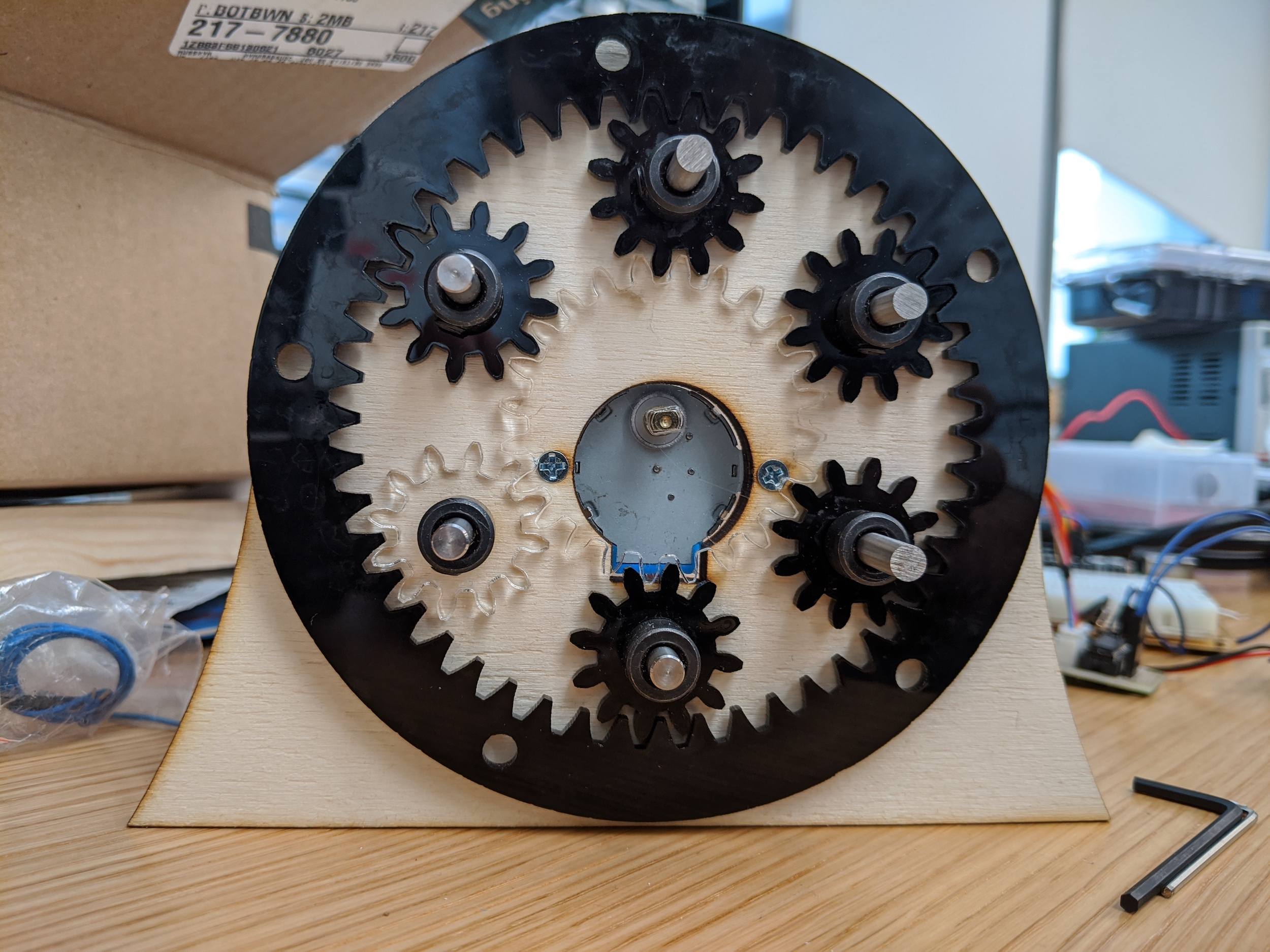 a set of laser cut acrylic gears in a planetary arrangement with six inner gears surrounded by one outer ring gear